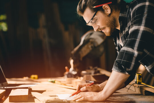 Happy Carpenter smiling to sketch design wooden furniture in wood workshop professional look high skill real authentic handcrafted working people.