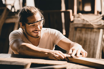 Fototapeta Young Carpenter happy working to making woodcraft furniture in wood workshop look professional high skill real people workman. obraz