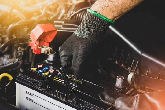 The Mechanic hand is pulling up an car old battery for replacement