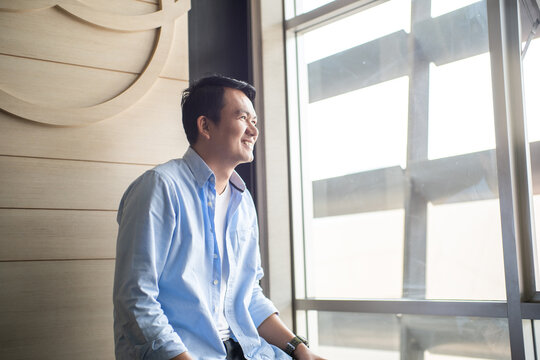 Portrait young man casual looking out window in office, Concept looking on future
