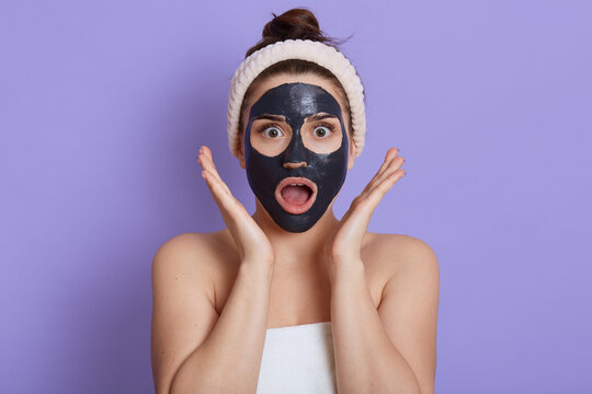 Photo of surprised speechless woman with opened mouth, wears mud facial mask, has beauty procedures, girl with shocked expression, wrapped towel on body, isolated on lilac wall, keeps palms near face.