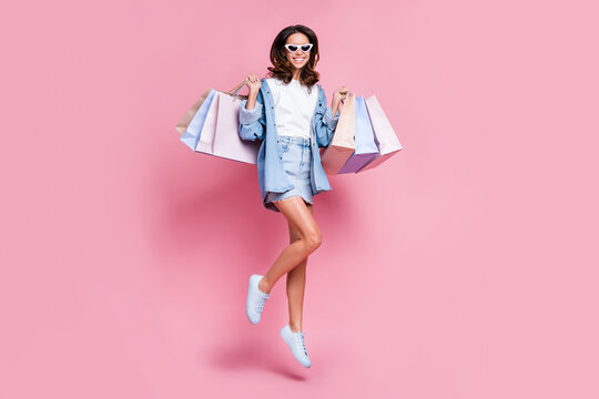 Full length photo of shiny lady dressed jeans clothes dark eyewear jumping high holding bargains isolated pink color background