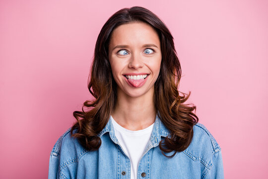 Photo of fooling cheerful cute young woman stick out tongue grimace isolated on pastel pink color background