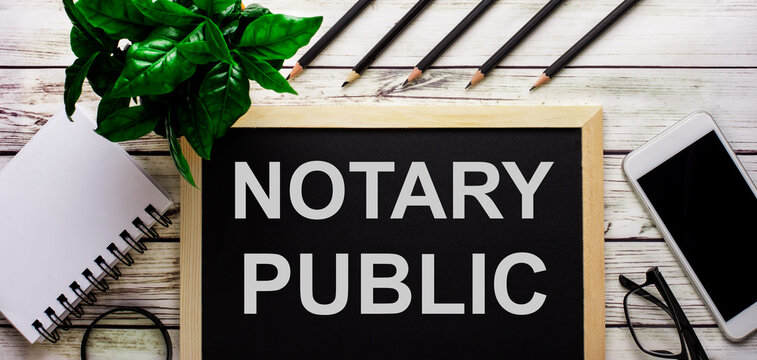 NOTARY PUBLIC is written in white on a black board next to a phone, notepad, glasses, pencils and a green plant.