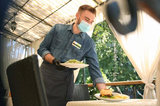 Waiter serving food in restaurant. Catering during coronavirus quarantine