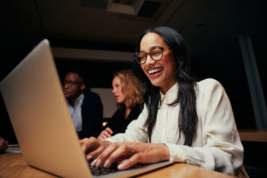 Close-up of successful smiling young African American businesswoman sitting near coworkers using laptop in office