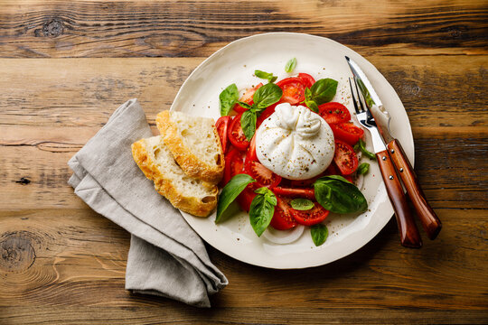 Salad with Burrata cheese, Tomatoes and Green basil on wooden background
