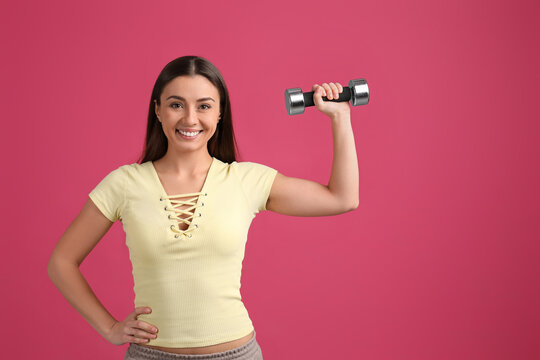 Woman with dumbbell as symbol of girl power on pink background, space for text. 8 March concept
