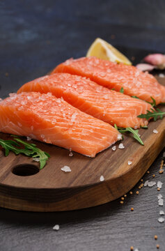 Raw fillet of salmon with sea salt, lemon and pepper on black stone background.