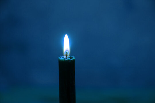 the flame of a burning candle on a blurred background