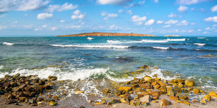 seascape with island in the distance. beautiful landscape of bulgaria near sozopol. waves crashing rocky shore. sunny weather with fluffy clouds on the sky