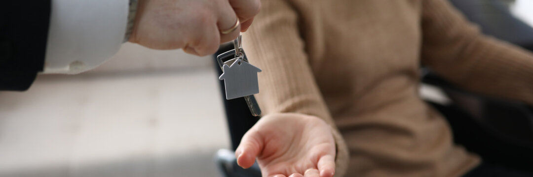 Close-up of male businessman giving keys from new house to disabled woman. Lady sitting in wheelchair. Moving day into apartment. Handicapped and real estate concept