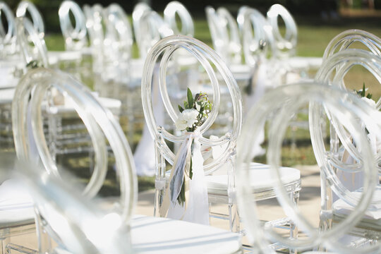 White transparent chairs at the wedding ceremony