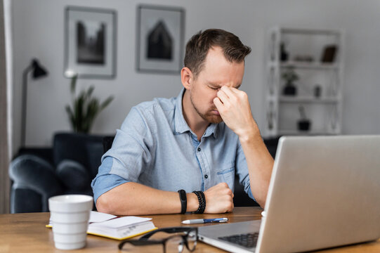 Overworked young entrepreneur in tired from work with a laptop, holds on to the bridge of the nose his eyes closed. Stressed guy works remotely at home feels eyes strain