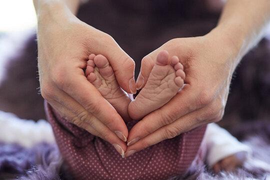 Babyfüße in den Händen der Mutter die ein Herz bilden