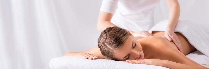 Fototapeta masseur massaging pleased young woman on massage table in spa salon, banner obraz