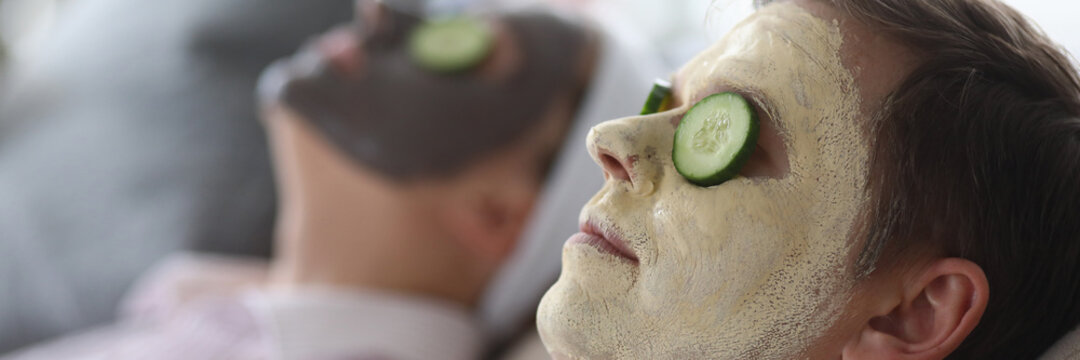 Close-up of wife and husband wearing cleaning and moisturizing face masks. Relaxed female and male laying on couch. Loving spouse with cucumber slices on eyes. Leisure and cosmetology concept