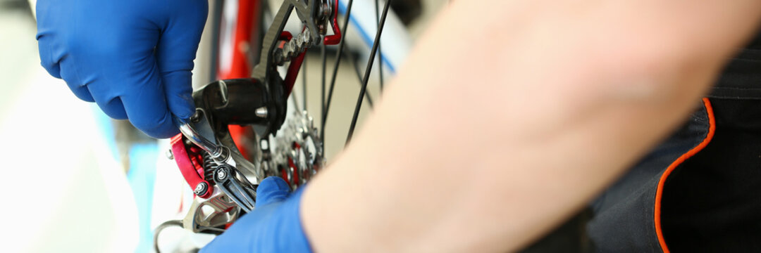 Close-up of mechanic serviceman installing assembling or adjusting bicycle gear on wheel in workshop. Technical expertise outdoors. Bike maintenance and repair service concept