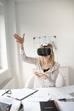 beautiful young female architect with virtual reality goggles is working in her office