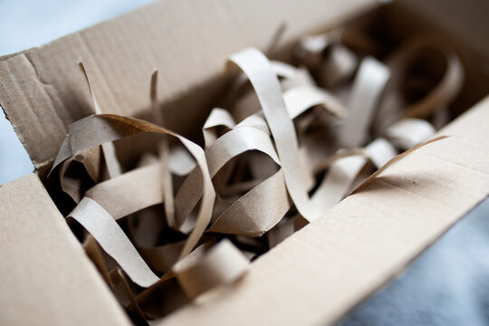 Cardboard box for eco gift filled with shredded paper. Eco-friendly gift packaging, paper filling.Opened cardboard box with shredded paper for gifting and stuffing.