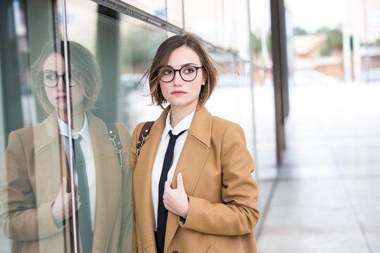 bella manager con camicia bianca, occhiali e cappotto in contesto urbano ,  garda seria riflessa in una parete a specchio