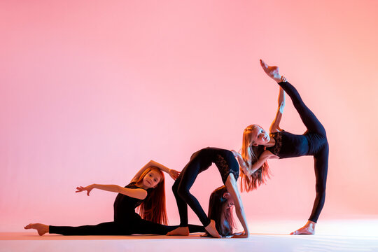 group of three ballet girls with long flowing hair in black tight-fitting suits dance on red background