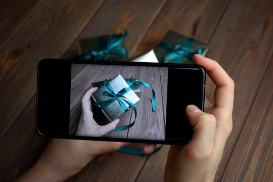 blogger takes pictures of gifts for subscribers on the phone. Giveaway