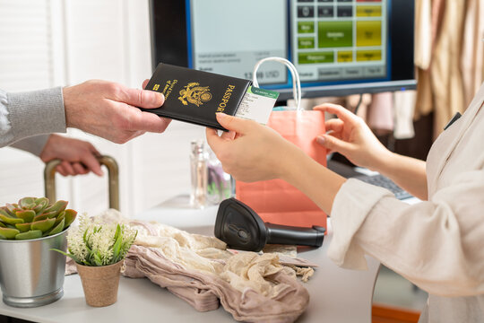 Man holding out american passport with boarding pass to cashier in female boutique store at the airport duty free.