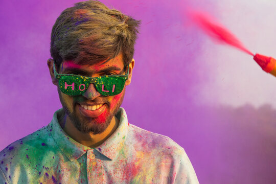 A HAPPY YOUNG MAN WEARING GOGGLES SMILING AT CAMERA WHILE CELEBRATING HOLI