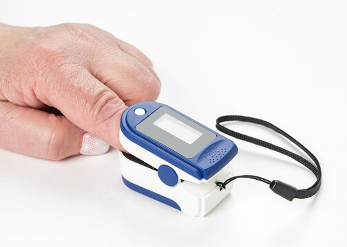 Portable digital fingertip pulse oximeter on a woman's hand isolated on white background.