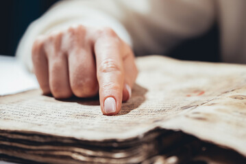 Woman reading ancient book - Bible. Concentrated attentively follows finger on paper page in...