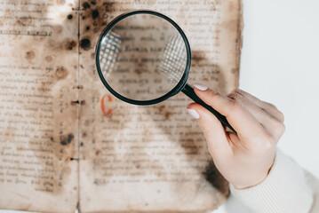 Woman researcher explores antique book with magnifier. Scientific translation of literature....