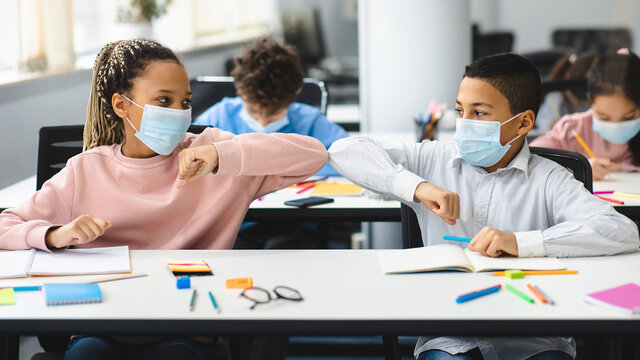 Diverse pupils wearing surgical face masks greeting and bumping elbows