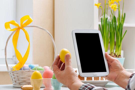 Senior woman holds Digital tablet mock up template for Easter app presentation or website promotion.