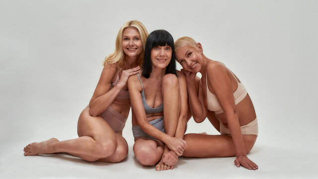 Three caucasian senior women in underwear smiling at camera while posing half naked in studio, sitting together isolated over light background