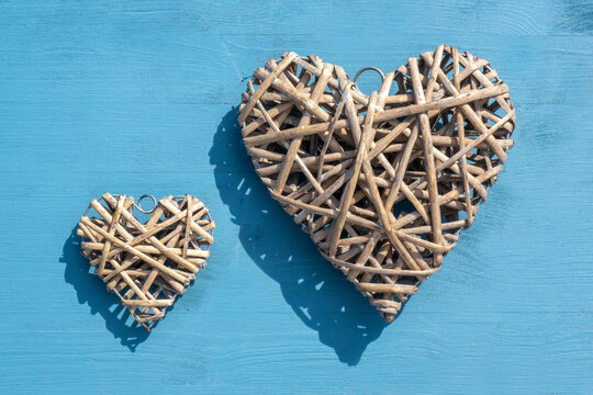 Celebration and special event concept: Top view on two separate, wooden heart shaped wreath. Distance small and big icon. Background in wooden blue. For lovers, friends, mothers and Valentines day