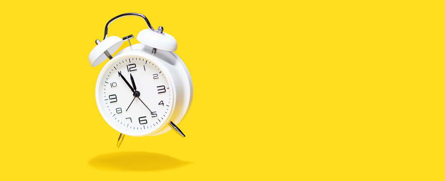 White bell alarm clock hovering over yellow background. 5 to 12 clock concept isolated