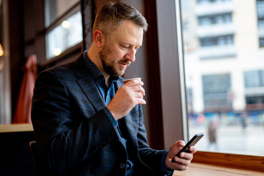 Authentic image of a pensive businessman in a coffee shop. Businessman in dark suit having break surfing internet on the phone.