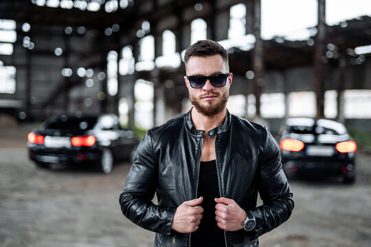 Strong athletic man fitness model. Guy in leather jacket and fashion glasses poses to the camera. Luxury black car on the background. Half length photo.