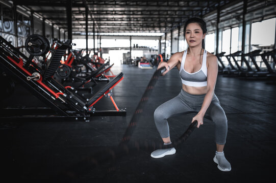 Asian strong woman exercising with battle ropes,A female workout alone at the gym