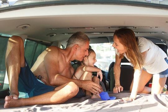 famiglia felice composta da papà mamma e figlia, in abbigliamento da mare si abbraccia felice vicino al furgone in mezzo a una strada