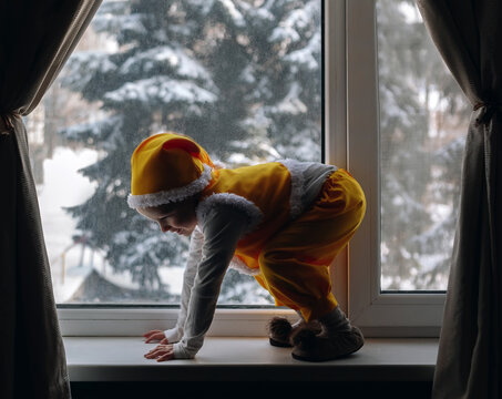 Little boy 4 years old play at window with winter view wear yellow
