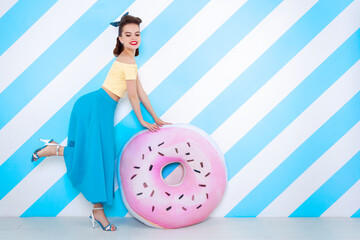 Sexy surprised woman with donuts in hands and open mouth. Colorful background in pop art retro comic style on striped blue background. Pinup and pop art concept