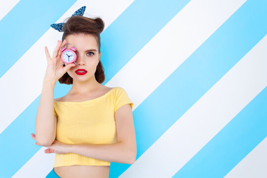 Sexy surprised woman with alarm clock in hands and open mouth. Colorful background in pop art retro comic style on striped blue background. Pinup and pop art concept