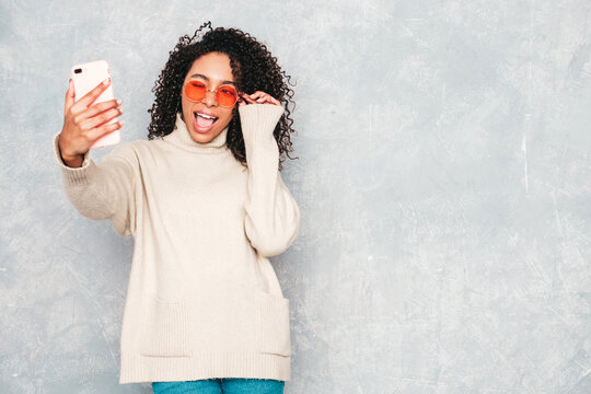 Beautiful black woman with afro curls hairstyle. Smiling model in white trendy sweater. Sexy carefree female posing near gray wall in studio interior.She taking selfie photos for instagram. Winking