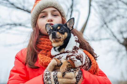 Girl in winter clothes. Teenager girl in an orange jacket, orange hat and scarf. Girl and chihuahua