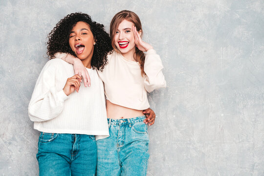 Two young beautiful smiling international hipster female in trendy summer jeans clothes. Sexy carefree women posing near gray wall in studio. Positive models having fun. Concept of friendship