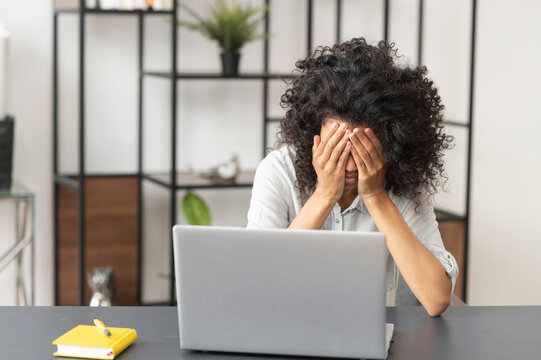 The deadline struggle, young African American female office worker manager with Afro hairstyle feeling tired, exhausted, and overworked, sitting with an open laptop and closing her face with hands