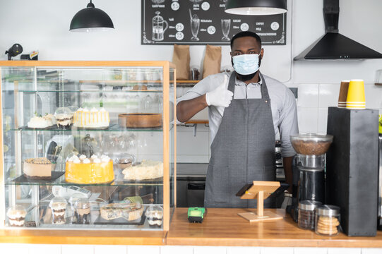 An African-American male waiter, cafe owner wearing mask and gloves stands and shows thumb up behind the counter. Protective measures of staff during quarantine lockdown