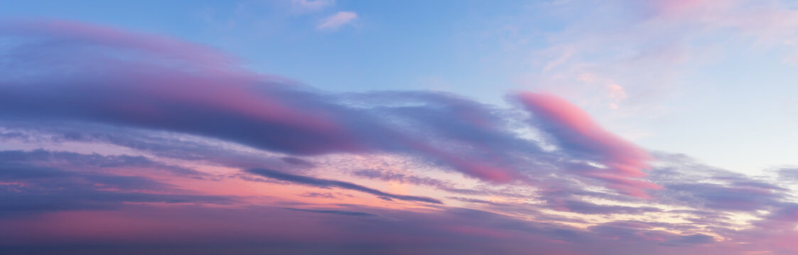 Scenic pink purple clouds against azure sky at sunset. Majestic vanilla sky panoramic shot. Beautiful pastel colored  evening skyscape. Paradise heaven.